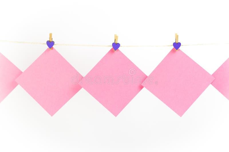 Розовые стикеры на веревке для белья с зажимками для белья изолированными на белой предпосылке стоковые фото
