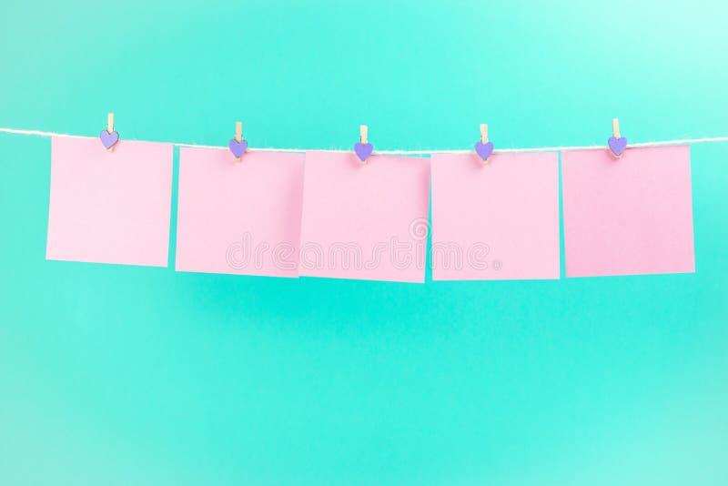 Розовые стикеры на веревке для белья с зажимками для белья изолированными на голубой предпосылке стоковая фотография