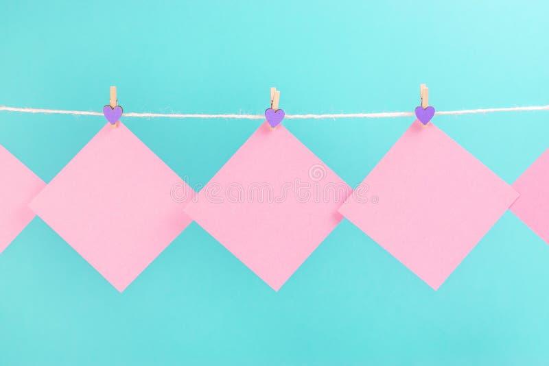 Розовые стикеры на веревке для белья с зажимками для белья изолированными на голубой предпосылке стоковое изображение
