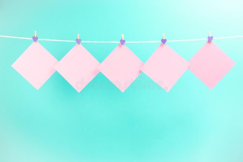 Розовые стикеры на веревке для белья с зажимками для белья изолированными на голубой предпосылке стоковое фото rf