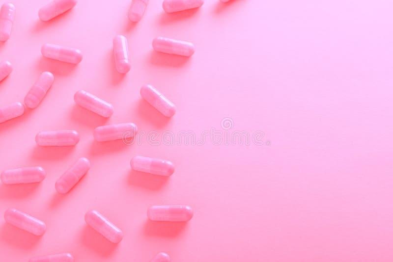 Розовые таблетки на розовом взгляде сверху предпосылки стоковое изображение rf