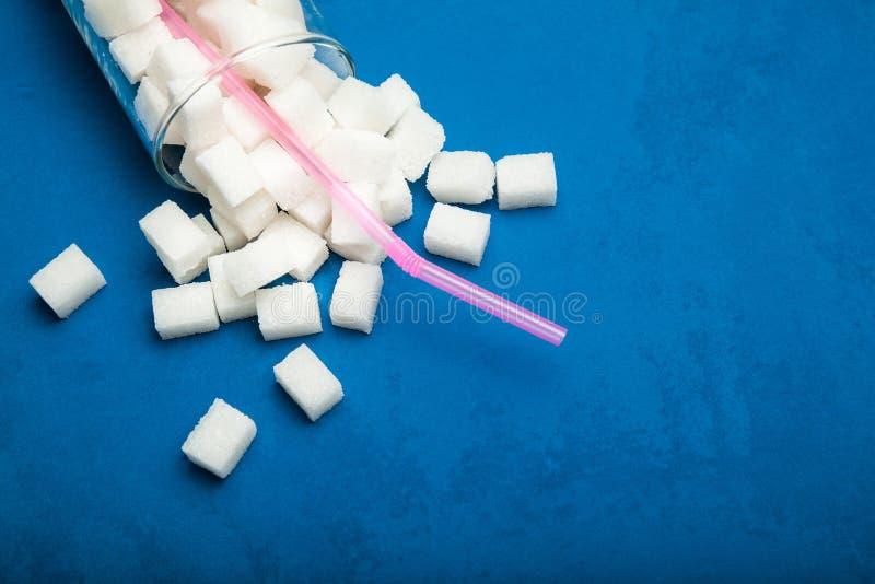 Розовые трубка и сахар коктейля в стекле на голубой винтажной предпосылке стоковые фотографии rf