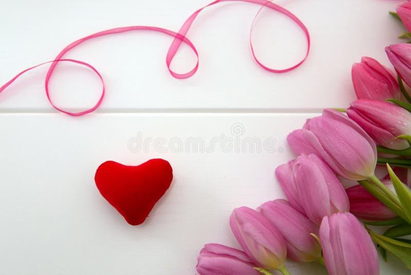 Розовые тюльпаны и полюбить сердце на белой деревянной предпосылке стоковое фото