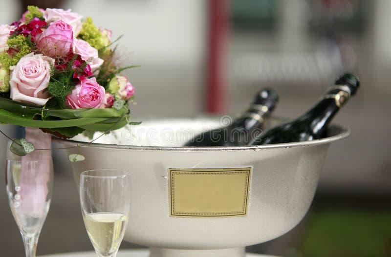 Розовые цветки морозят охлаженную бутылку игристого вина и шампанского в космосе текста copyspace ведра стоковые фото