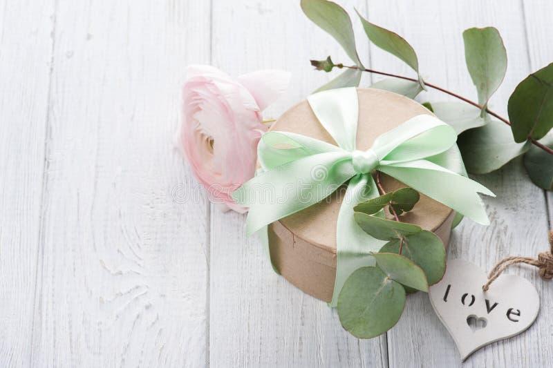 Розовые лютик и подарочная коробка с зеленой лентой стоковая фотография
