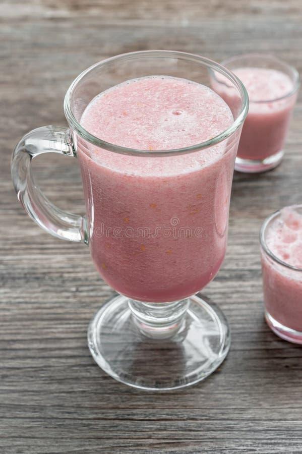 Розовые smoothies ягоды питья Smoothies в больших и малых стеклах на деревянном столе стоковые изображения
