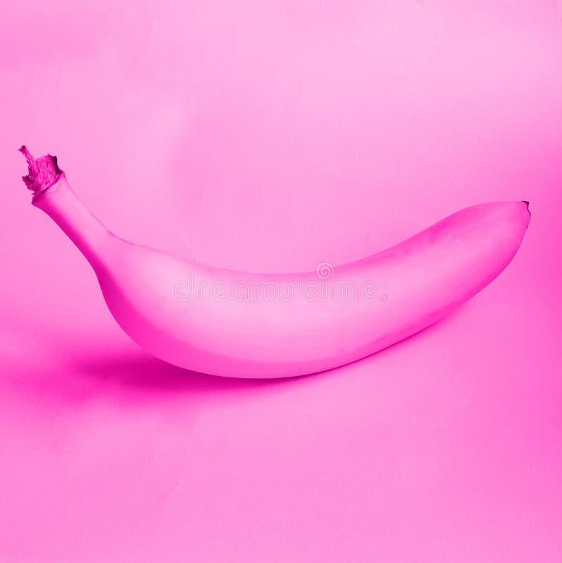 Розовый банан лежа на розовой предпосылке Flirty фото плода стоковые фотографии rf