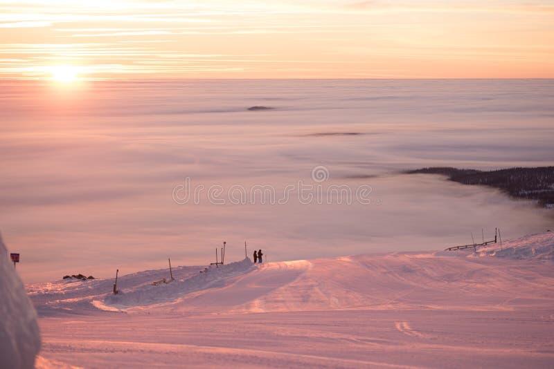 Розовый заход солнца na górze горы Идет снег совсем вокруг, красота лыжного курорта стоковое изображение