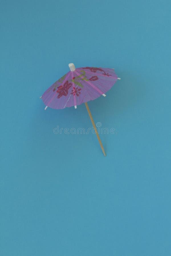Розовый зонтик для коктеиля на предпосылке голубой бумаги Conceptua стоковая фотография rf