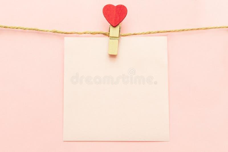 Розовый лист чистого листа бумаги на бельевой веревке и clothespegs с красным сердцем на розовой предпосылке r стоковое фото