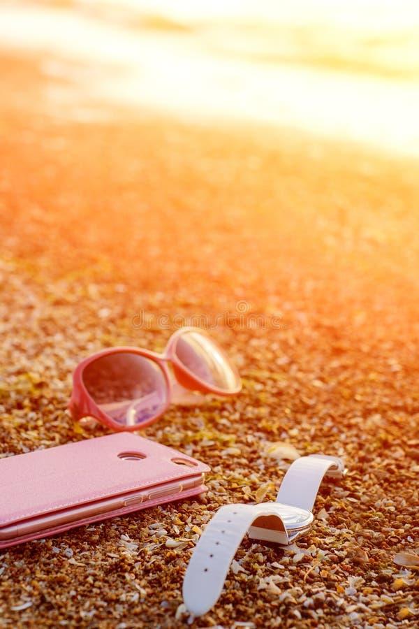 Розовый мобильный телефон, белые наручные часы и розовые стекла на пляже моря Sandy с волнами и солнечным светом самомоднейший те стоковое фото rf