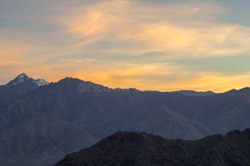 Розовый оранжевый заход солнца золота над долиной гор стоковые фото