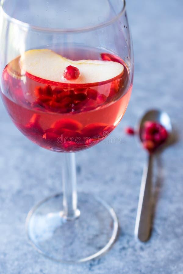 Розовый пинк краснеет коктеиль вина с семенами гранатового дерева, куском Яблока и задавленным льдом стоковые фотографии rf