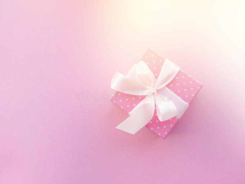 Розовый подарок рождества с лентой, на розовой предпосылке стоковые фото