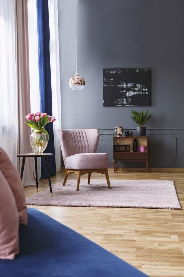 Розовый стул рядом с таблицей с цветками в элегантной живущей комнате int стоковые фото