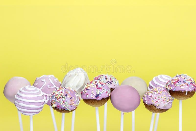 Розовый торт хлопает на желтой предпосылке стоковое изображение