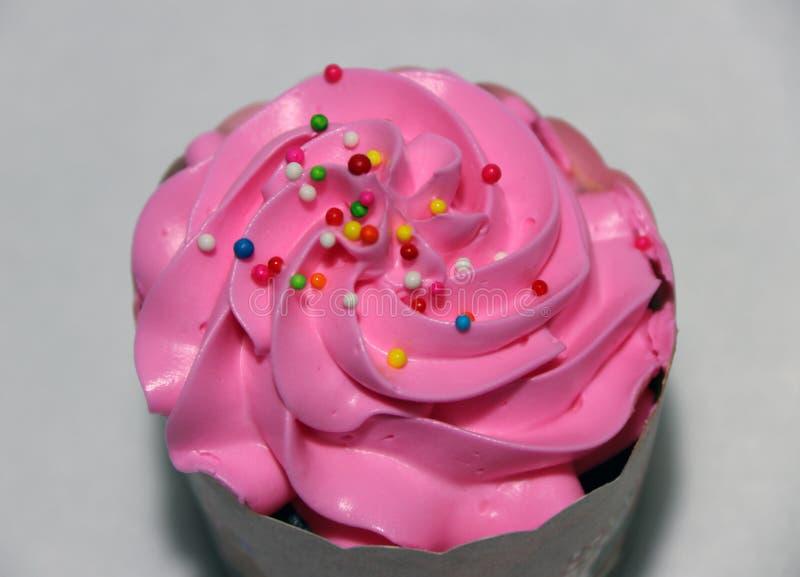 Розовый торт чашки на белой предпосылке с красочным округленным сахаром отбортовывает на сливк стоковая фотография