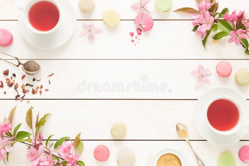 Розовый fruity чай и пастельные французские торты macarons на белизне стоковое фото rf