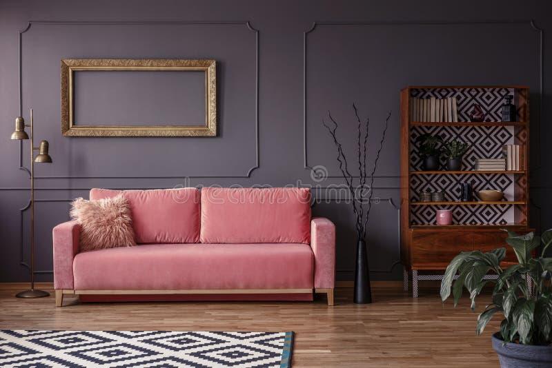 Розовый settee против серой стены с модель-макетом рамки золота в elega стоковое фото rf