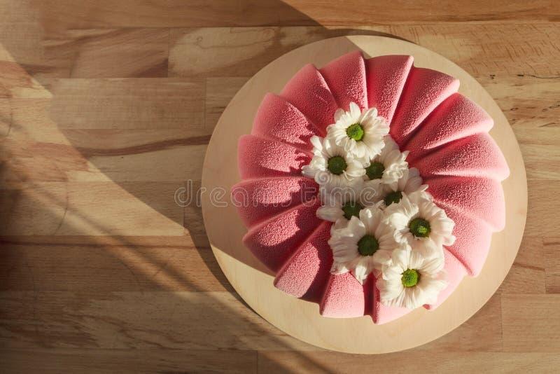 Розовым велюр украшенный тортом и белые стоцветы в деревянной предпосылке стоковое изображение rf