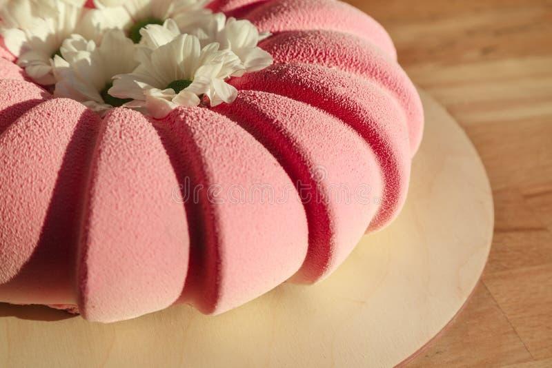 Розовым велюр украшенный тортом и белые стоцветы в деревянной предпосылке стоковые изображения