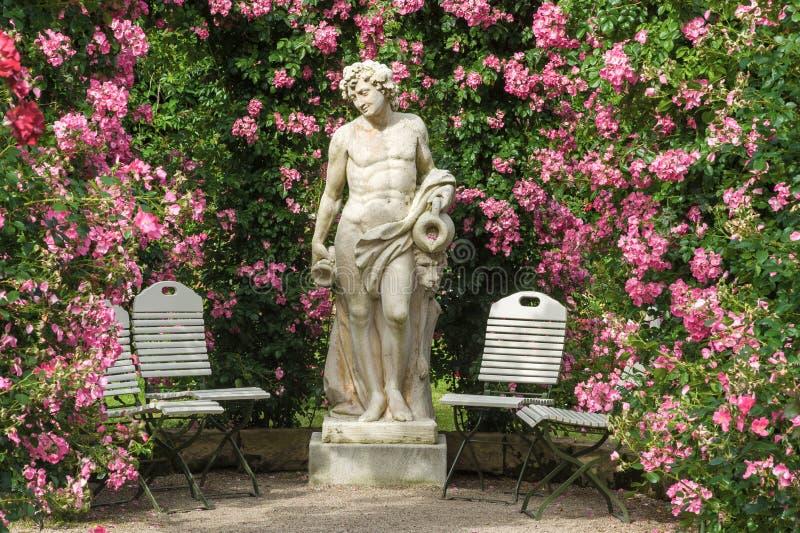 Розы и статуя богов в розарии Beutig в Баден-Бадене стоковые изображения