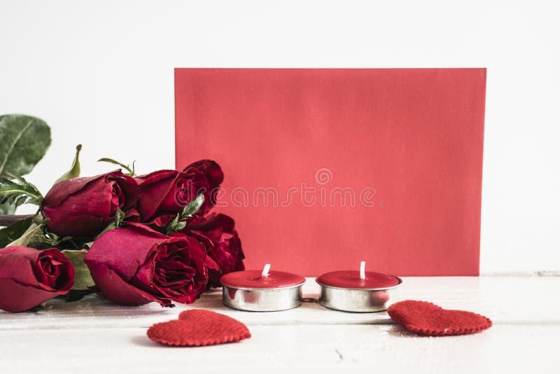 Розы, красная форма сердца, свечи и красная бумага на белой таблице C стоковое фото rf