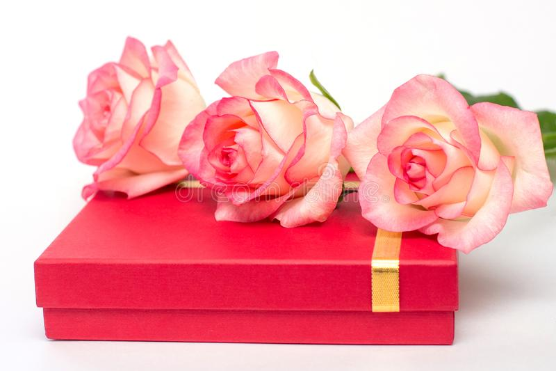 3 розы лежат на красной басовой коробке Подарки на белой предпосылке Подарок для любимого стоковая фотография