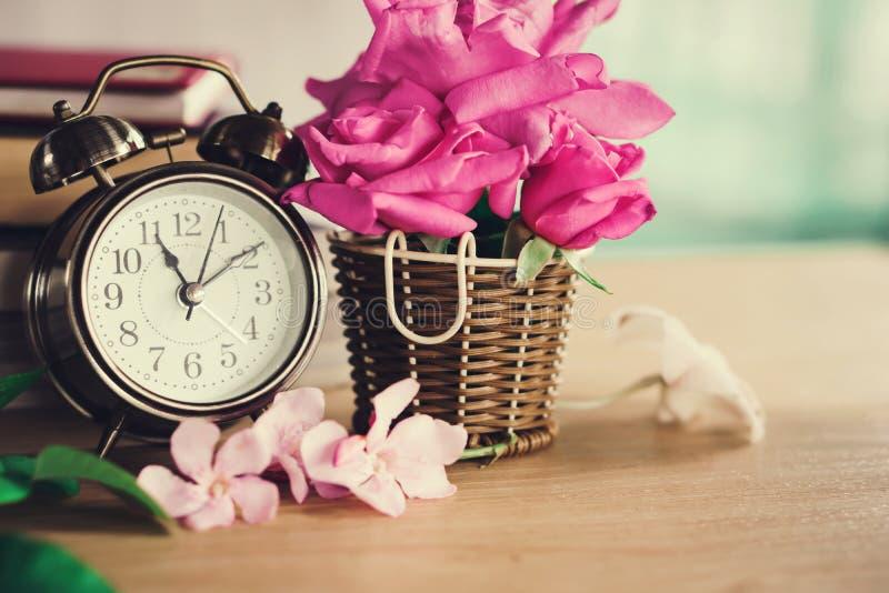 Розы цветут букет с часами на деревянном столе стоковые фотографии rf