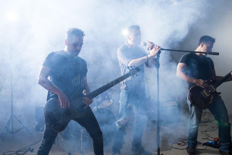 Рок-певец и гитаристы на этапе стоковые фотографии rf