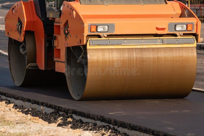 ролик компактирует асфальт на дороге во время конструкции дороги уплотнение мостовой в строительстве дорог каток стоковое фото rf