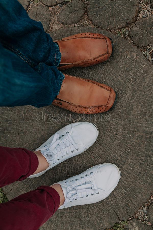 Романс лета Ноги человека и женщины на деревянной дорожке стоковые фото