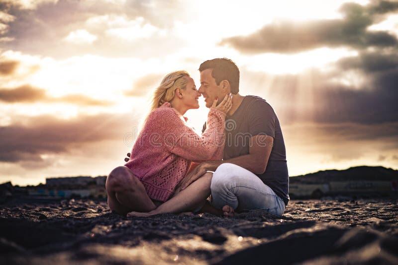 Романтический сценический момент и концепция любви с парой молодых красивых людей, обнимающихся и целующихся, сидят на земле с стоковые изображения rf
