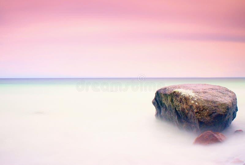 Романтичная атмосфера в мирном утре на море Большие валуны вставляя вне от ровного волнистого моря Розовый горизонт стоковая фотография