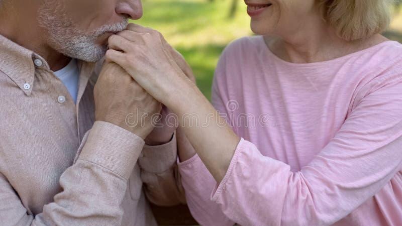 Романтичная достигшая возраста рука жены человека целуя, на открытом воздухе дата в парке, счастливые отношения стоковые изображения rf