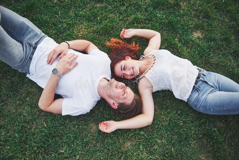 Романтичная пара молодых людей лежа на траве в парке Взгляд сверху стоковые фотографии rf