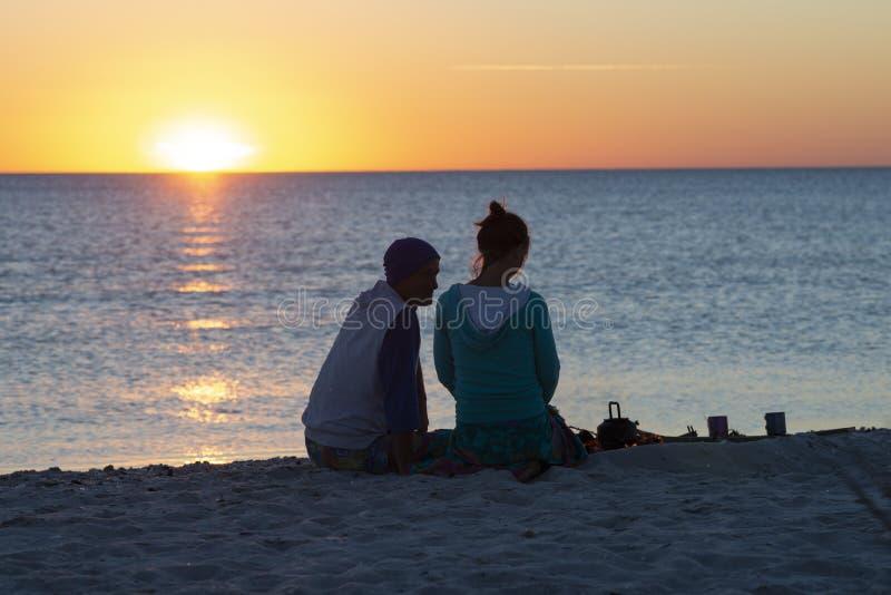 Романтичная пара ослабляет на пляже, выпивает кофе стоковое фото