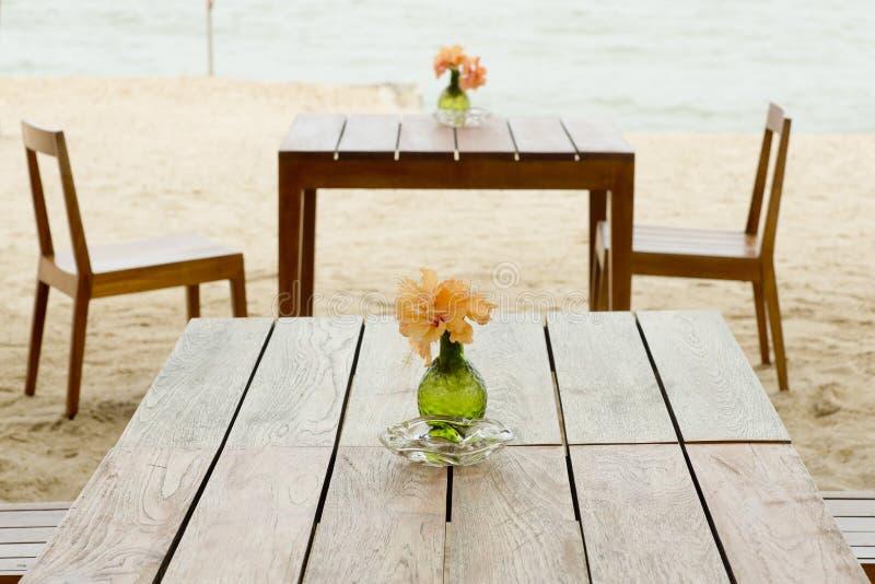 Романтичная таблица настроенная на тропическом пляже стоковые фото