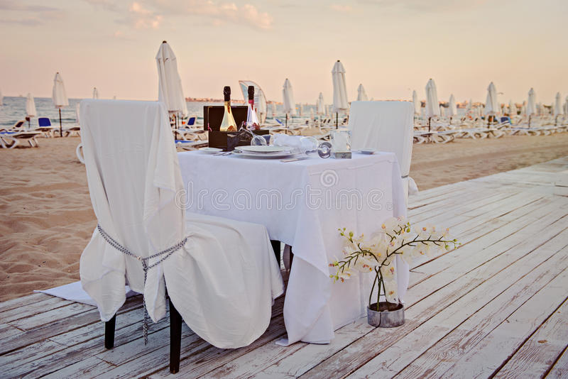 Романтичная установка обедающего, на пляже с заходом солнца стоковое фото rf