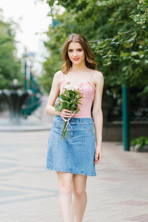 Романтичное изображение маленькой девочки идя вдоль улицы лета города в парке с букетом роз стоковое изображение