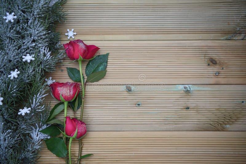 Романтичное изображение фотографии рождества при красные розы и украшение гирлянды взбрызнутое с снегом на деревянной предпосылке стоковое фото rf