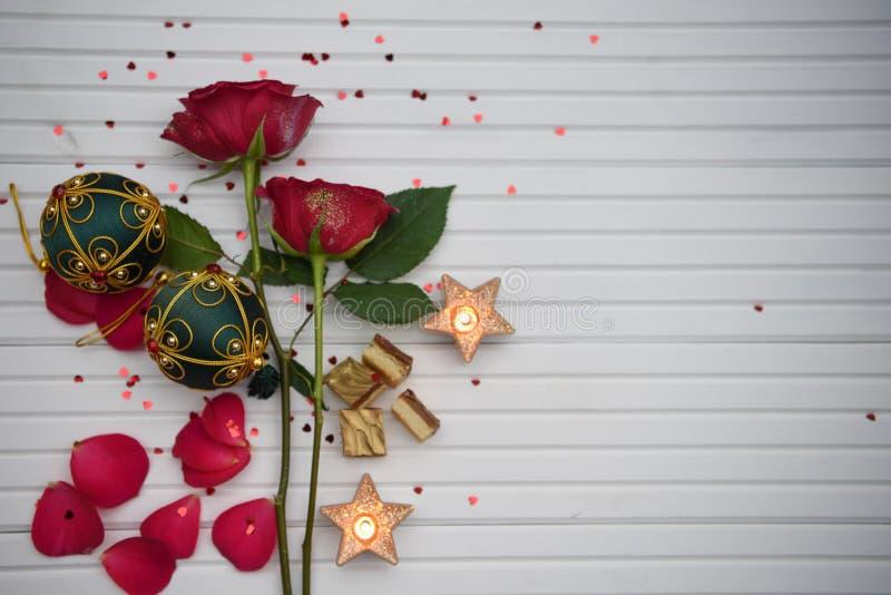 Романтичное изображение фотографии рождества цвета с красными розами осветило свечи и роскошный шоколад с красными и зелеными укр стоковые изображения