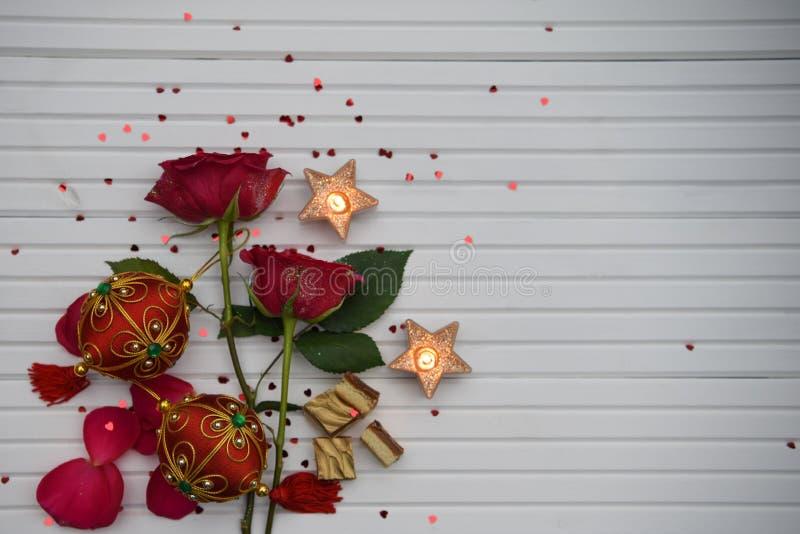 Романтичное изображение фотографии рождества цвета с красными розами осветило свечи и роскошный шоколад с красными и зелеными укр стоковые фотографии rf