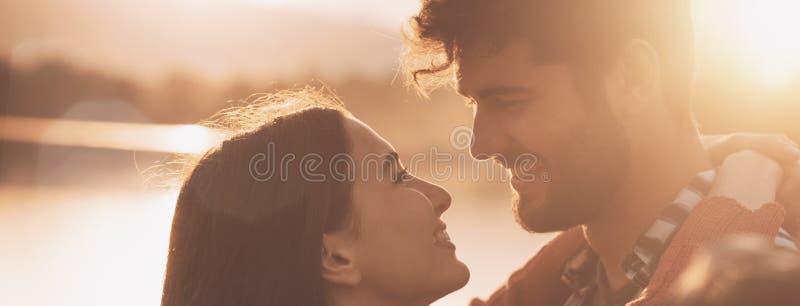 Романтичные любящие пары целуя на заходе солнца стоковые фотографии rf