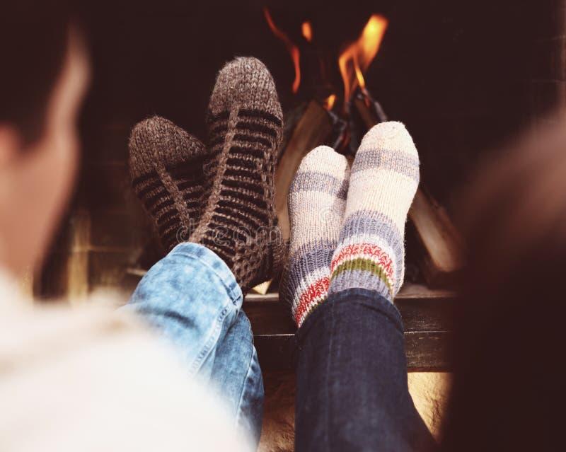 Романтичные ноги пары в носках перед камином на wint стоковое фото rf