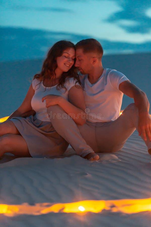 Романтичные пары в любов сидя на песке в пустыне Вечер, свечи горит в песке в форме сердца вокруг их стоковые изображения