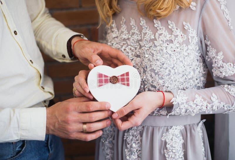 Романтичные пары держа подарочную коробку в форме сердца в их руках против кирпичной стены стоковое изображение