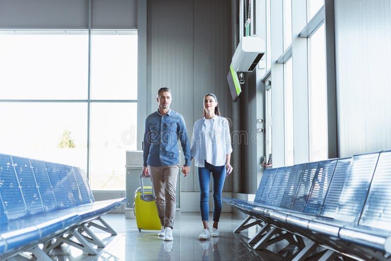 Романтичные пары держа руки идя с желтым багажем стоковая фотография
