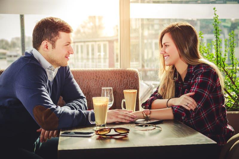 Романтичные пары держа руки на кофейне стоковое изображение