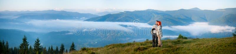 Романтичные пары наслаждаясь утром haze над горами стоковое фото